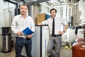 """Gabriel Muschert, Geschäftsführer der Springbach-Mühle, und Progas-Fachberater Marco Kneisel (li.) vor dem """"neotower""""-Blockheizkraftwerk."""