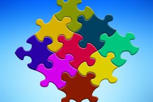 Bunte Puzzleteile vor blauem Hintergrund.