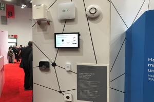 Komponenten des Coqon Smart-Home-Systems auf einem Messestand.
