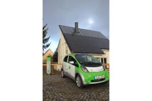 Ein Elektroauto tankt am energieautarken Haus auf.
