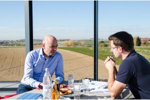 Zwei Männer sitzen sich an einem Tisch gegenüber.