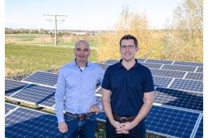 Zwei Männer stehen vor Solarmodulen.
