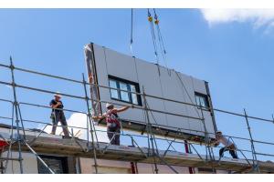 Ein vorgefertigtes Fassadenelement wird auf eine Baustelle gehievt, drei Arbeiter helfen.