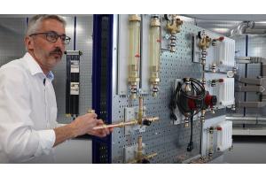 Ein Mann erklärt etwas an einer Montagewand für Rohrsysteme.