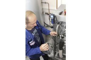 Ein Installateur schließt eine Blase mit Betriebsgas an ein Messgerät an.