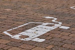 Weißes Symbol für ein Elektroauto auf Steine gemalt.