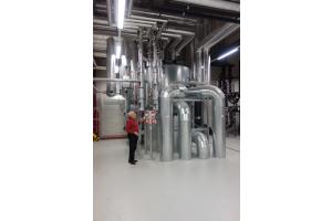 """5-stufige """"Zortström""""-Lösung (Heizung). Die Anlage mit einem Durchmesser von 2,2 m stellt Wärmeenergie in fünf Temperaturzonen zwischen 35 und 90 °C zur Verfügung. Integrierte Erzeuger sind drei BHKW, zwei Gaskessel sowie zwei Abgaswärmeübertrager und ein Wärmerückgewinnungsmodul."""