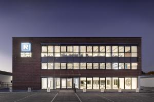 Beleuchteter Hauptsitz der Rehms Gruppe von außen.
