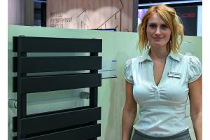 Eine Frau steht neben einem Design-Heizkörper.