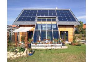 Ein Haus mit PV-Anlage auf dem Dach.