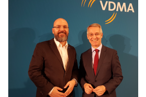 Zwei Männer stehen vor einer blauen Wand mit den weißen Buchstaben VDMA.