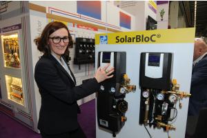 """Eine Frau steht neben einer """"SolarBloC""""-Solarstation."""