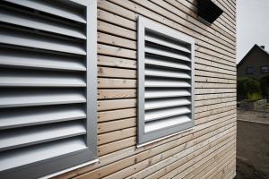 Außenwand eines Hauses mit Gittern vor den Zu- und Abluftöffnungen einer Wärmepumpe, darüber der Lufteinlass einer KWL-Anlage.