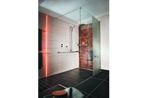 """Das Bild zeigt einen Ausschnitt des GGT-Musterbades. In der bodengleichen Dusche, die mit der elektrischen Temperierung ausgestattet ist, kommt die Entwässerungsrinne Schlüter """"Kerdi-Line"""" mit einer Rinnenabdeckung aus Edelstahl zum Einsatz. Der Boden ist mit schwarzen Fliesen ausgelegt."""