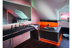 """Das Bild zeigt einen Ausschnitt des GGT-Musterbades. Das Bad verfügt über einen Waschtisch über eine gemütliche, mit Fliesen von Agrob Buchtal ausgestattete Wellnesszone, die sich dank der elektrischen Temperierung """"Ditra-Heat-E"""" von Schlüter zeitgenau erwärmen lässt."""