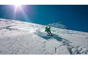 Ein Mann fährt auf Skiern eine Piste hinunter.