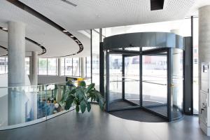 Karusselltürsysteme sorgen an den Haupt- und Nebeneingängen für die Fortführung der ästhetischen Durchgängigkeit der Glasfassade.