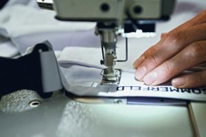 Das Bild zeigt eine Nähmaschine, auf der ein Kleidungsstück mit einem Firmenlogo gefertigt wird.