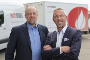 Zwei Männer stehen vor einer mobilen Heizzentrale von Hotmobil.