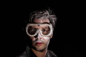 Ein Mann mit einer Schutzbrille vor schwarzem Hintergrund.
