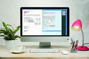 Ein Computer-Bildschirm, der auf einem Schreibtisch neben einer Tastatur, Lampe, Pflanze, Tasse und einem Stiftebecher steht.
