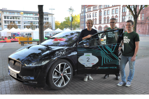 Drei Männer stehen neben einem Auto.