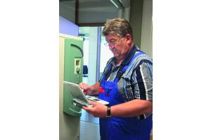 Das Bild zeigt einen Handwerker mit Laptop.