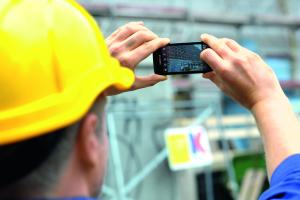 Das Bild zeigt einen Handwerker mit Handy in den Händen.