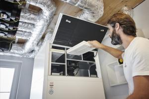 """Die Haustechnikzentrale vereint Wärmeerzeugung, Warmwasserbereitung, bei Bedarf heizende Lüftung sowie Kühlung in einem bodenstehenden Gerät. Der Wartungsaufwand für die Kombianlage """"Genius"""" beschränkt sich im Wesentlichen auf den Luftfilterwechsel, hier durch Hausherr Philipp Schrenk."""