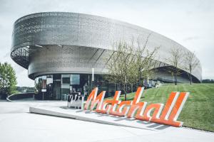 """Die """"KTM Motohall"""" in Mattighofen bietet für jeden Besucher ein einzigartiges Erlebnis. Perforierte Metallbänder, ein Sinnbild von Reifenabdrücken, umkurven den modernen Stahlbetonbau."""