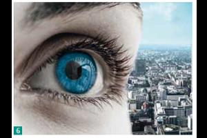 Ein Auge in Nahaufnahme vor einer Stadt.