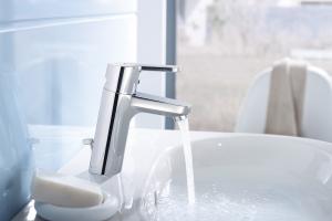 """Das Bild zeigt die verchromte Waschtischarmatur """"HansaPrimo"""" von Hansa, aus der Wasser in ein weißes Waschbecken fließt."""
