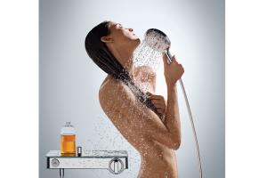 """Das Bild zeigt eine Frau, die in der Hand die Handbrause der Serie """"Raindance Select S 120"""" von Hansgrohe hält. Aus der Handbrause fließt Wasser auf den Körper der Duscherin."""