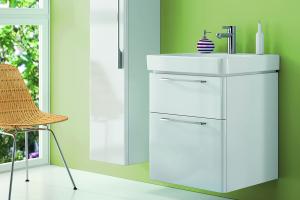 """Das Bild zeigt ein Bad, das mit dem Möbelprogramm """"Smyle"""" von Keramag ausgestattet ist. Mittig im Bild ist der weiße Waschtisch-Unterschrank zu sehen, auf dem ein weißes Keramikbecken montiert ist."""