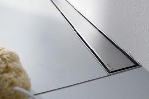 """Das Bild zeigt die Edelstahl-Duschrinne """"ACO ShowerDrain"""" von ACO, die vor einer weißen Wand in einem weiß gefliesten Boden installiert ist."""