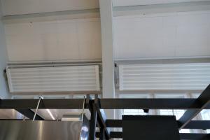 """Die Deckenstrahlplatten """"KSP Akustik"""" sind jeweils in die Zwischenräume der tragenden Konstruktion eingepasst. Die Aufhängung in der Schräge wurde mit U-Profilen aus Stahl und dem Drahtseilsystem """"Gripple"""" umgesetzt. Der Platz für Anschlüsse und weitere Bauteile war limitiert."""