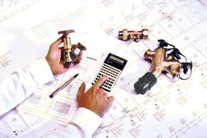 TGA-Fachplaner sitzt über einem komplexen Haustechnikplan