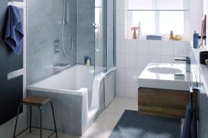 """Das Bild zeigt ein Badezimmer, an dessen linker Wand sich die Duschwanne """"Dobla"""" von HSK befindet. Die grauen Wandpaneele besitzen das gleiche Design wie die Wannenverkleidung."""