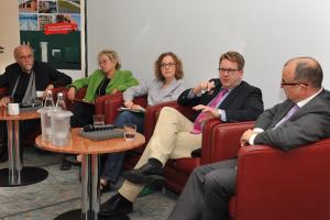 Podiumsdiskussion mit fünf Teilnehmern.