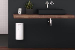 """Das Bild zeigt den weißen Komfort-Durchlauferhitzer """"DHE Connect"""" von Stiebel Eltron, der dezent unter einem Waschtisch an einer grauen Wand angebracht wurde."""